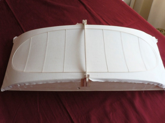Figure 2. The vacuum box used to cover the completed wing frame is shown below. The completed dry structure is presumably tacked to the balsa carrier, which locates into slots on either side of the jig for exact positioning. The hole in the side of the box is to accept the clear plastic tube seen in figure 4 and the top of the box is covered with soft thin porous fabric.